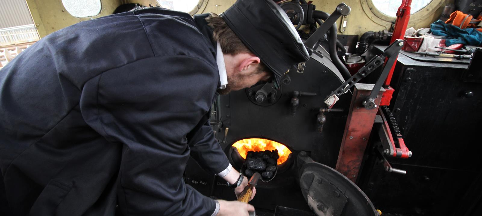 The fireman shovelling coal on the footplate of our steam locomotive
