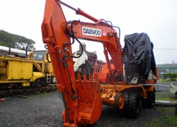 The newly arrived Daewoo Road/Rail excavator sitting in the station yard. The damaged cab can be seen undercover.