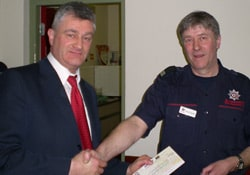 John Beaumont receives the donation from David Dryden, Downpatrick Station Commander
