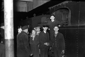 Passengers say farewell to the BCDR at Ardglass Station, with the last train on the branch between Downpatrick and Ardglass, which closed on 14th January 1950, the night before the main line. Pictured: J. Hamilton (driver, bottom right), B. Savage (fireman, top, standing), W. Irvine (porter/guard, second from right) J. Hamilton retired in 1981, B. Savage went to the UTA buses, retired 1981 as well, W. Irvine left for England.