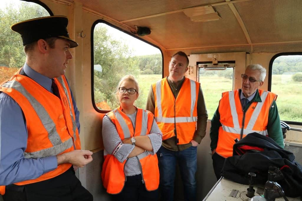 In the cab of the locomotive, Robert Gardiner (DCDR Chairman) explains the expansion plans to Emma Rogan MLA, Chris Hazzard MP, while DCDR Board Member Albert Hamilton looks on.